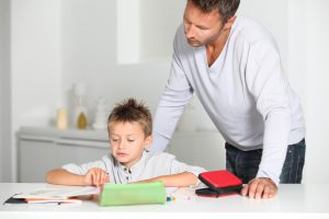Father helping son to do homework