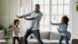 Happy father have fun teaches little preschool kids to dance in modern living room at home. Dad with son and daughter engaged in funny activity enjoy leisure carefree weekend concept